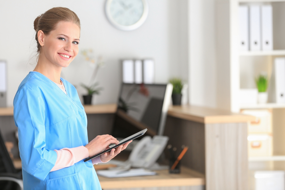 Young female receptionist holding tablet computer in hospital