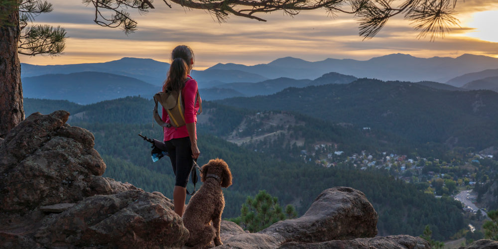 woman is hiking with a dog in the Rocky Mountains